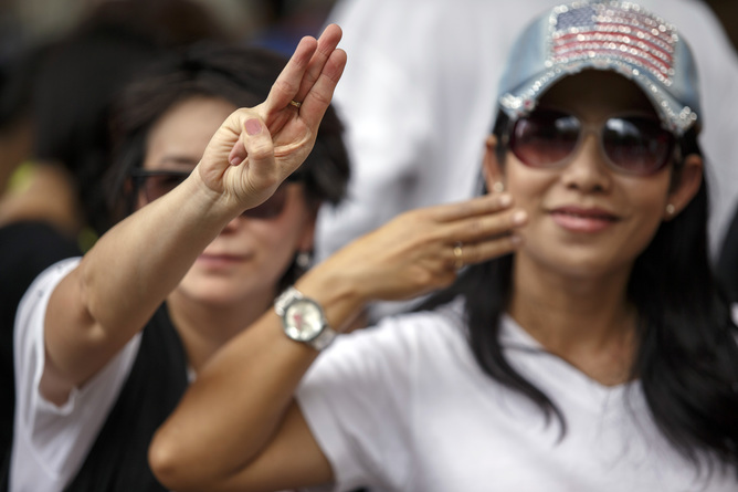 "Pro-U.S. demonstrators make the three-fingered gesture salute inspired by ""The Hunger Games"" movie, as they rally outside the U.S. embassy in Bangkok"